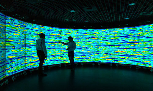 Scientists conferring in front of turbulence fluid flow simulation screens.